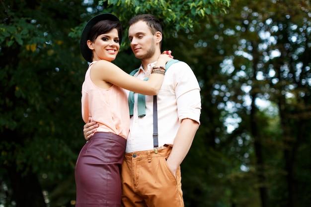 Молодой парень держит своего возлюбленного за талию, девушка счастлива с улыбкой на лице