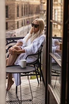 Девушка в белом халате сидит на балконе и наслаждается. сексуальная девушка в белом халате на балконе летом. винтажный цвет
