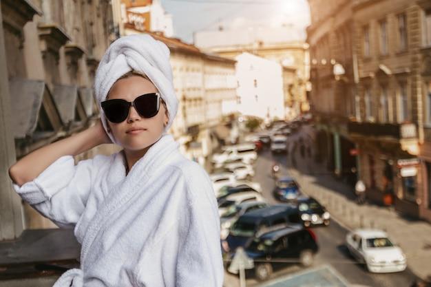 Девушка в белом халате и полотенце на голове в темных очках стоит на балконе у городской стены