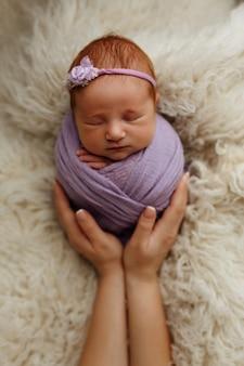 生まれたばかりの赤ちゃんは、母親の腕の中で繭のポーズ(ジャガイモ袋)で寝ています。安全と幸福の概念