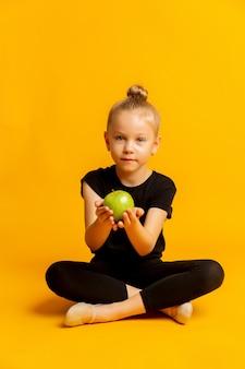 Понятие о детском спорте и здоровом питании. счастливая жизнерадостная взволнованная уверенная девушка-гимнастка держит зеленое свежее яблоко, изолированное на ярко-желтом фоне