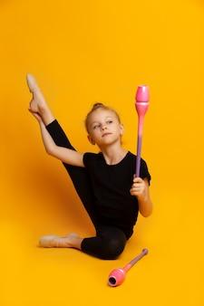明るいスタジオで杖で踊る小さな体操選手