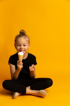 美しい小さな女の子の子供は、水着とダンスシューズで黄色の背景にワッフルコーンでバニラアイスクリームをかみます。コピースペース
