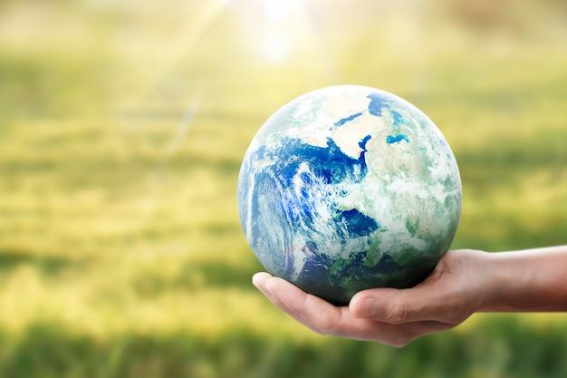Глобус, земля в руке, держит нашу планету светящейся. изображение земли предоставлено наса