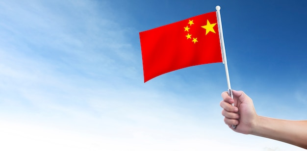 空気中の中国の旗を持っている手