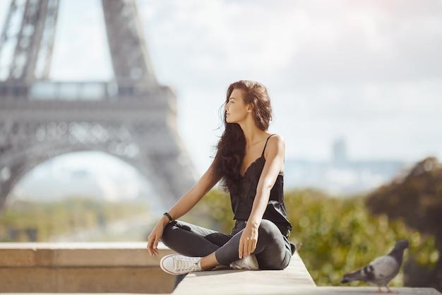 パリのエッフェル塔の近くの美しい若い観光客の女の子。