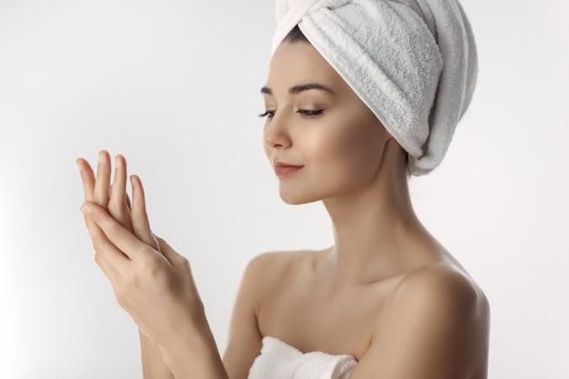 Свежая и красивая брюнетка женщина, применяя крем для рук