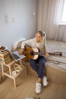 Девушка играет на гитаре дома