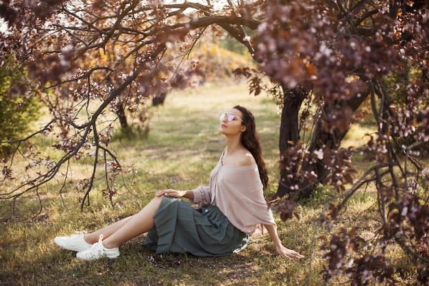 Женщина на открытом воздухе в парке возле весеннего цветущего дерева