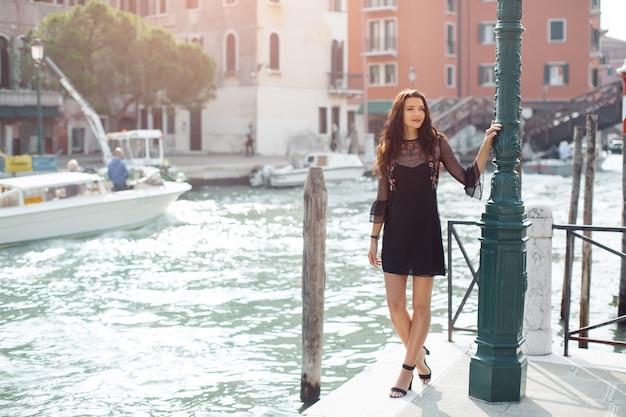 桟橋に立っている黒いドレスの女
