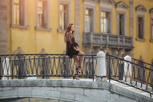 橋の上に座っている黒いドレスの女