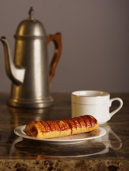 Ананасовый фаршированный хлеб с чайником, чашка чая.