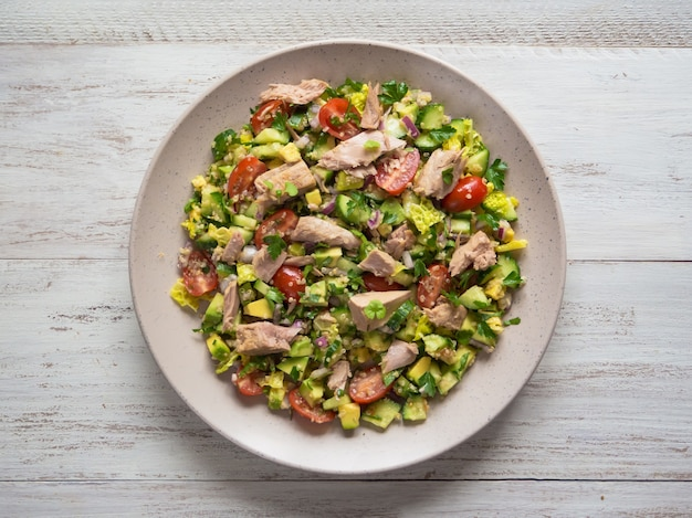 Салат с авокадо и тунцом. зеленый органический салат с кусочками консервированного тунца.