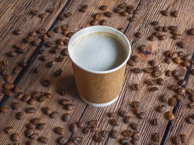 Кофе в бумажном стаканчике лежит на коричневом столе.