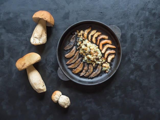 ペニーパンを調理します。黒いテーブルの上の鉄鍋で揚げたセペス。上面図。