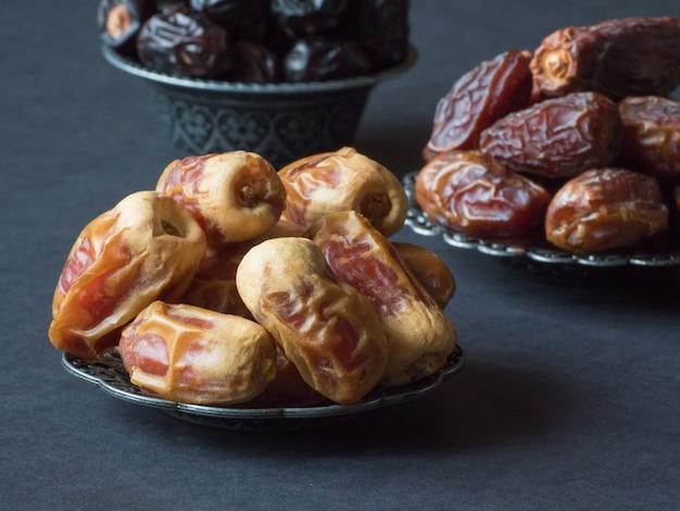 アラビアのナツメヤシの果実は、暗いテーブルの上に配置されています。閉じる。