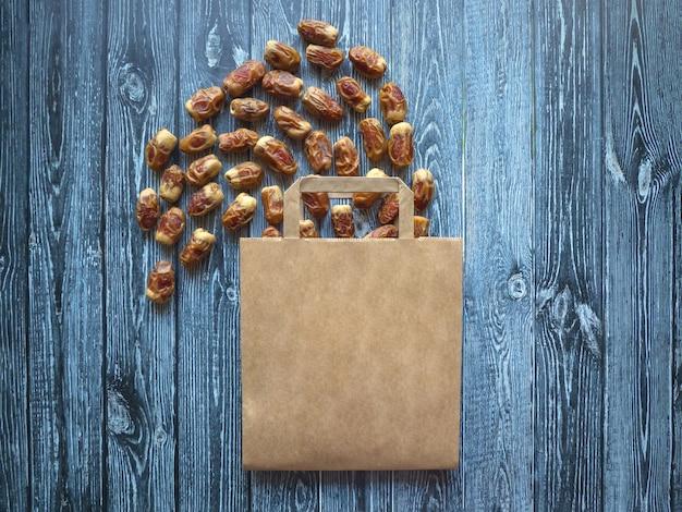 Финики фруктов выложены на деревянный стол с сумкой.