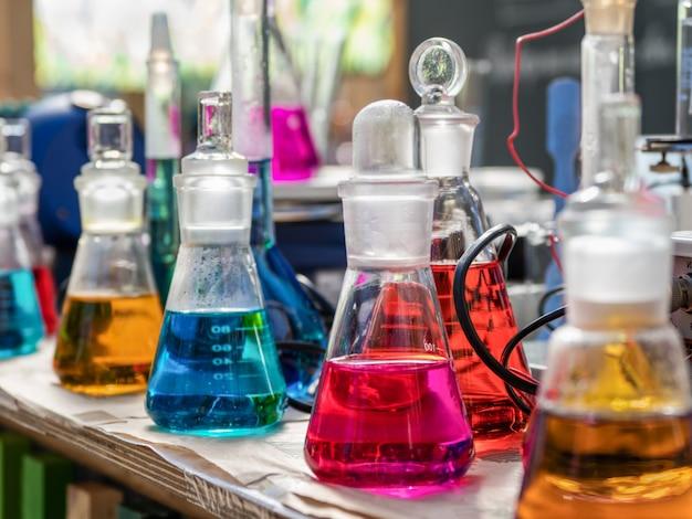 テーブルの上の着色された試薬が付いているフラスコ。