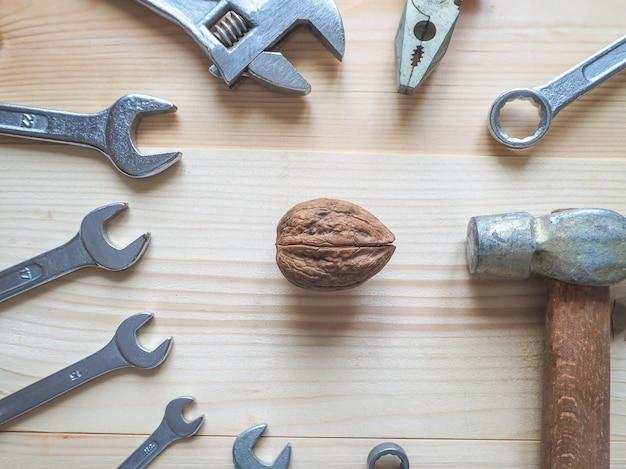 Инструмент и грецкие орехи на деревянный стол. концепция сложных проблем, которые необходимо решить.