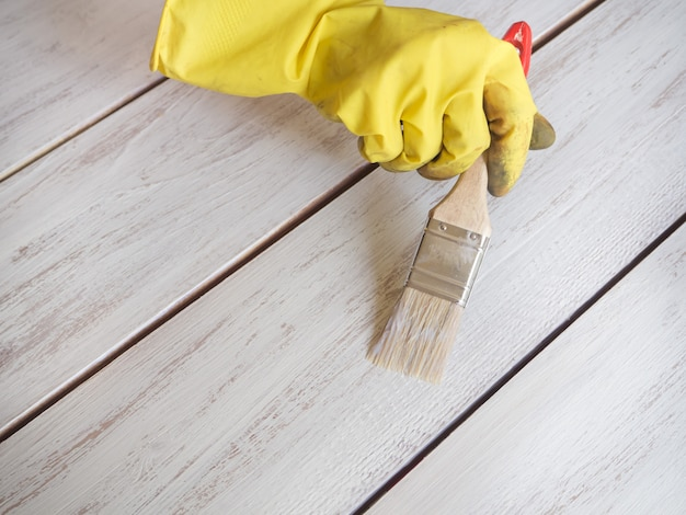 塗装の修理作業。彼の手でペイントブラシは床をペイントします。