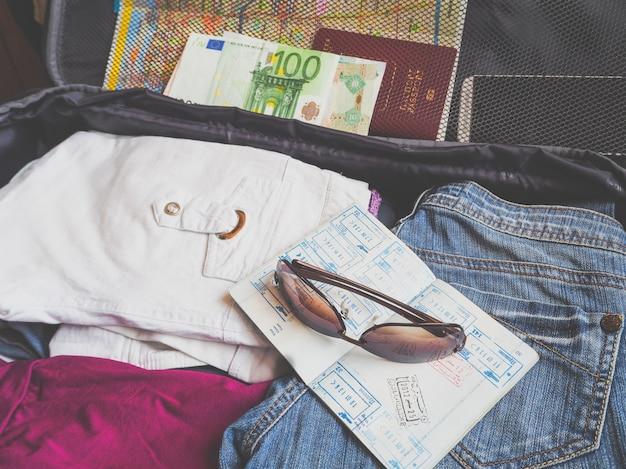 旅行用のスーツケースに集められたビザとお金のパスポート。旅行のコンセプト。