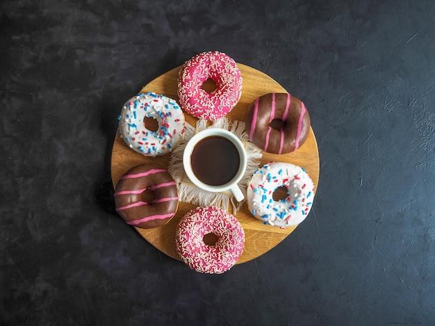 Чашка кофе и пончики на черном столе