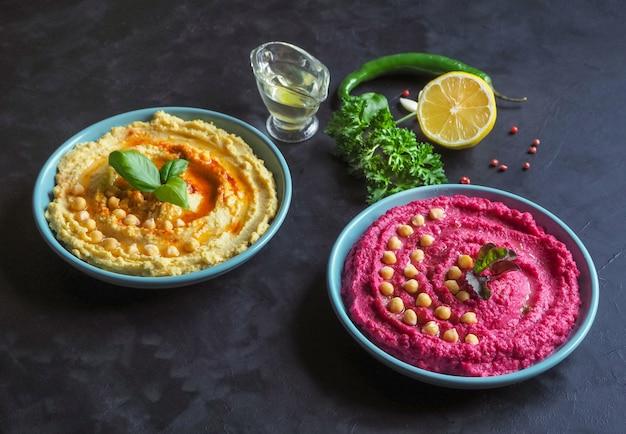 Хумус со свеклой и традиционным хумусом на черном кухонном столе