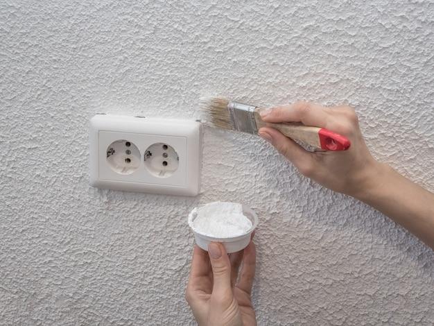 壁を塗る女性。塗られた白い壁の修復。