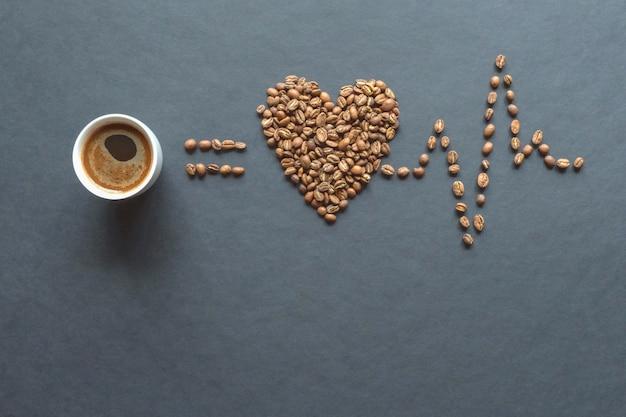 Кардиограмма кофейных зерен и чашка кофе на черном столе.