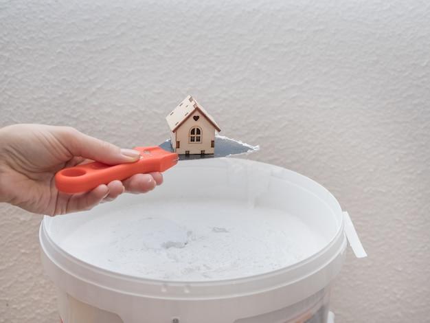 Шпатель и игрушечный домик. концепция ремонта в квартире.