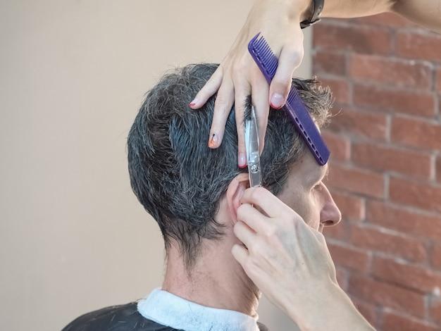 理髪店の椅子に座って、美容師は彼の髪を散髪します。理髪店。