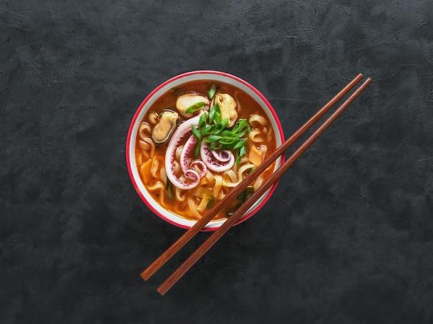 Очень вкусный пряный суп лапши морепродуктов с палочками на черной таблице. вид сверху.