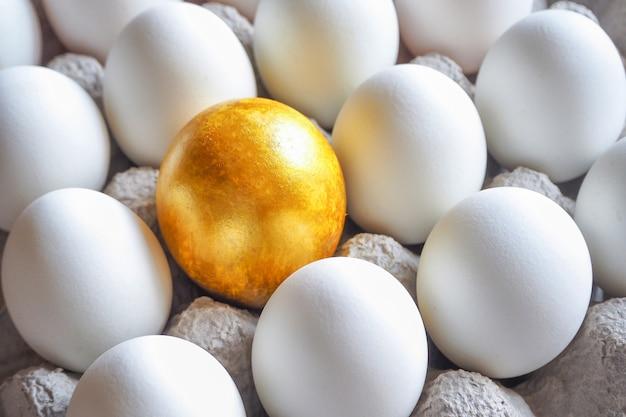 カートンパックの白い鶏の卵の中で黄金の卵。