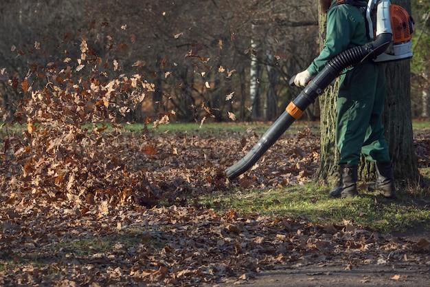 Мужской рабочий удаляет лист воздуходувки газон осеннего сада.