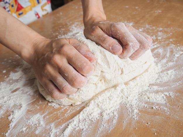 Приготовление теста женскими руками в пекарне