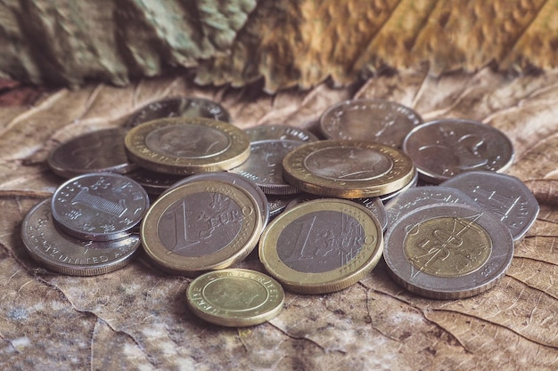 さまざまなお金のコインがヴィンテージのテーブルに積まれています。