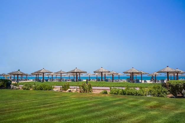 休暇の休日のビーチ。ドバイのアラビア湾の海岸にあるサンベッドとサンシェードのあるビーチ