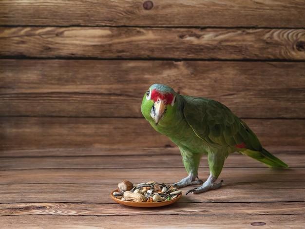 オウムの食べ物は木製のテーブルに散らばっています。食べ物を食べる緑のアマゾンオウム。