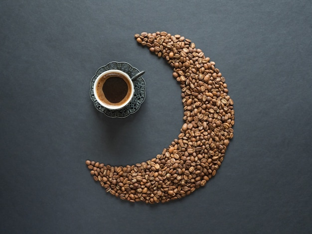 コーヒー豆と黒いテーブルの上のブラックコーヒーのカップで作られた三日月形。上面図。