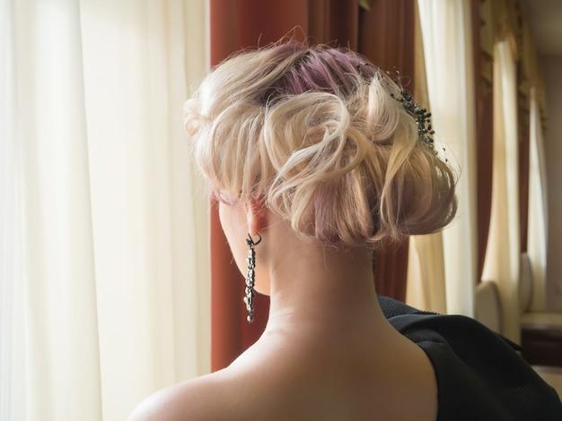 Белокурая женщина с красивой прической с аксессуаром детали волос, вид сзади крупного плана.