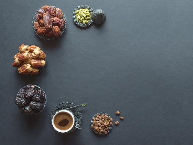 フルーツの日付と黒いテーブルの上のカルダモンとアラビアコーヒーのカップ。