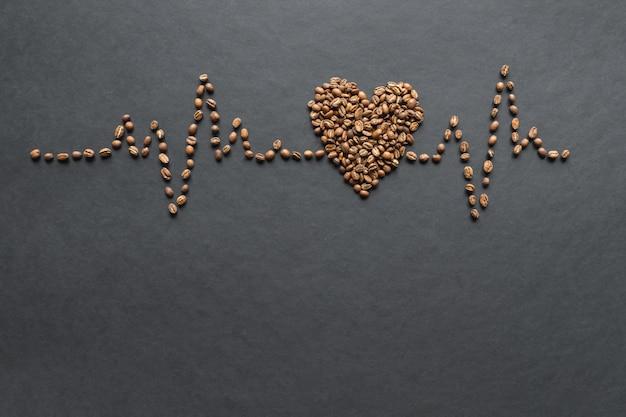 Кардиограмма кофейных зерен на черном столе.