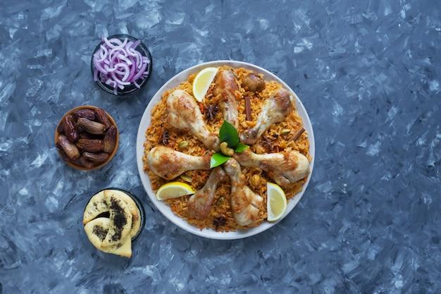 黒いテーブルの上の日付とチキンマンディ。アラビア料理。上面図。