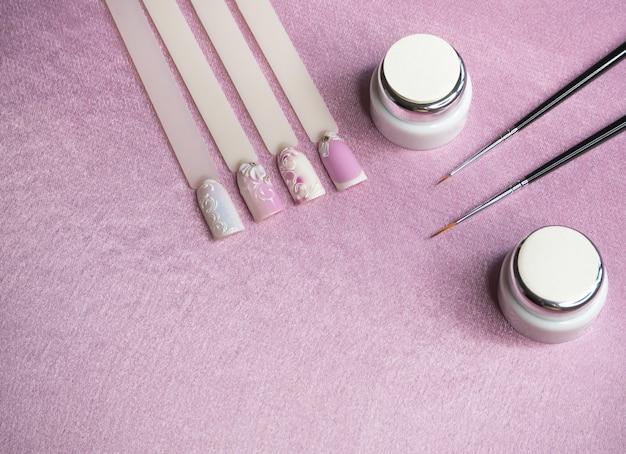 ピンクのテーブルに爪を描くためのヒントとペイント。創造的なマニキュアのコンセプト。