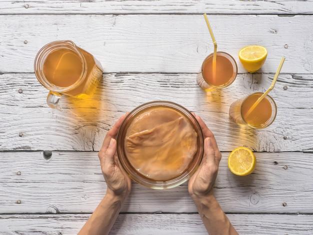 コンブチャ菌。白い木製のテーブルに有機発酵茶飲料。