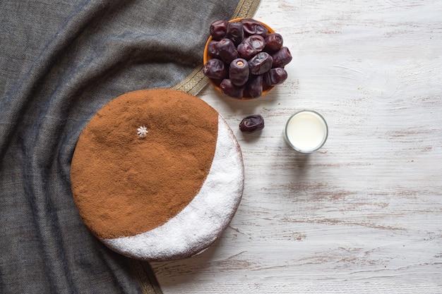 牛乳、ナツメヤシ、一杯のコーヒー、美味しいナツメヤシのケーキと三日月。ラマダンの背景。