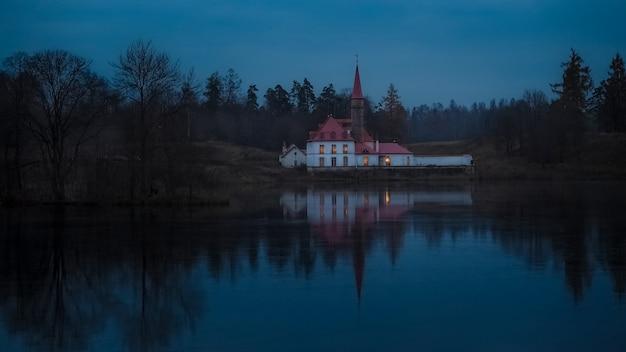 古い城のある神秘的な夜の風景は、湖と森に反映されています。ガッチナの古代の町。