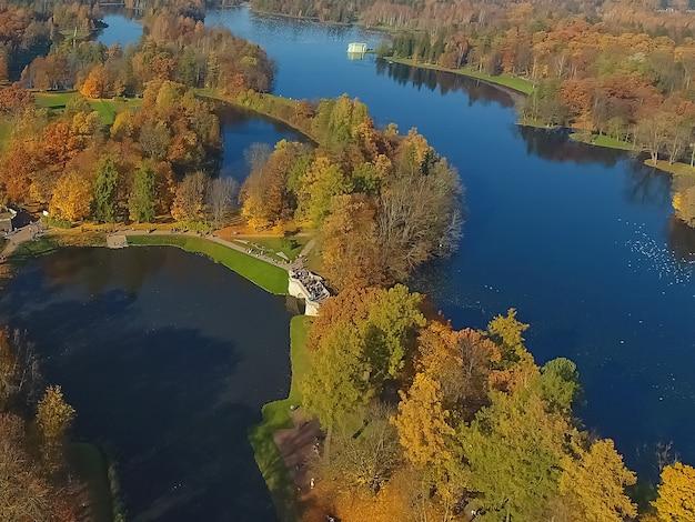 Аэрофотоснимок парка осенью. вид на озеро и лес сверху. гатчина. россия
