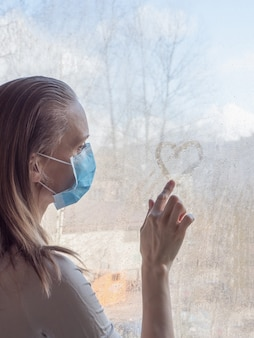 検疫、コロナウイルスのパンデミック。悲しいことに窓辺に立っている医療用使い捨てマスクを身に着けている女性が濡れたガラスの上にハートを描く