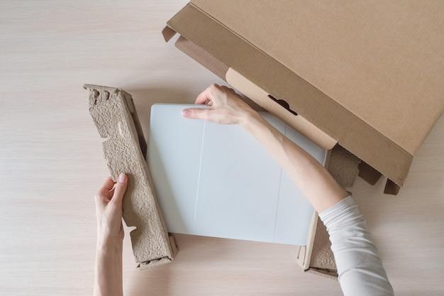 段ボール箱から新しいラップトップを開梱します。手が箱を開けます。受け取った小包の開梱